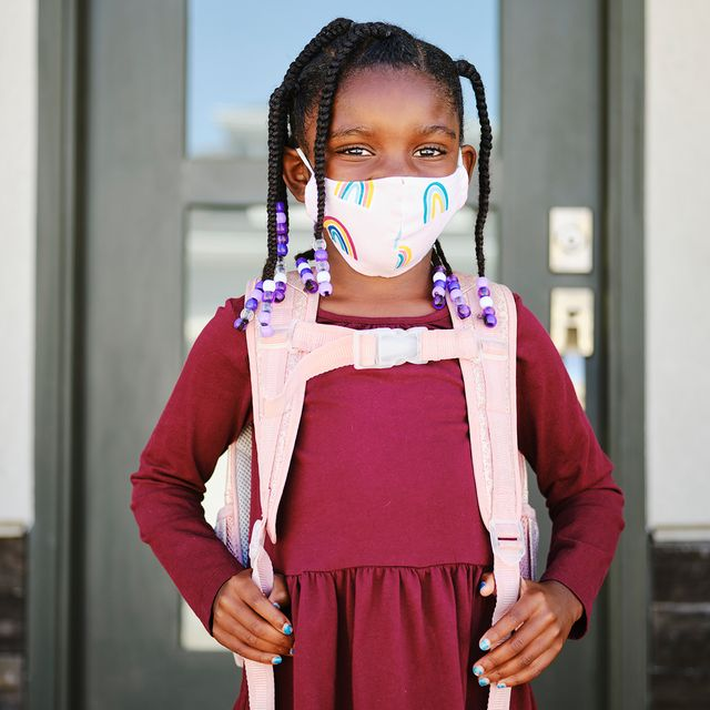 young girl wearing face mask and backpack in front of school