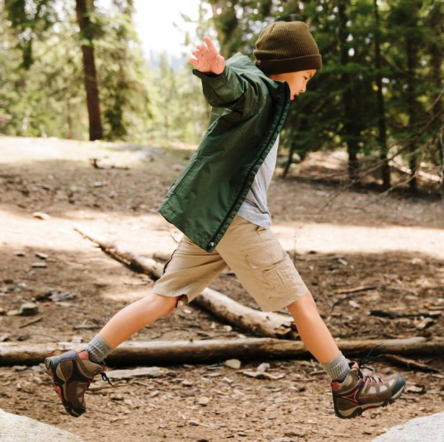young boy jumping between two rocks in the woods