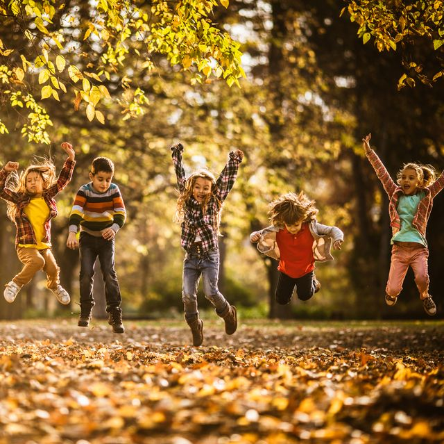 large group of playful kids having fun while jumping during autumn day in nature copy space