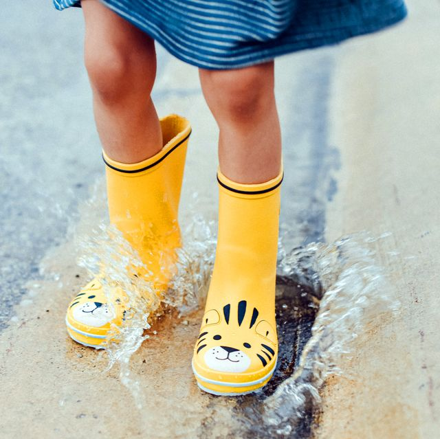 kid jumping in puddle wearing yellow rain boots
