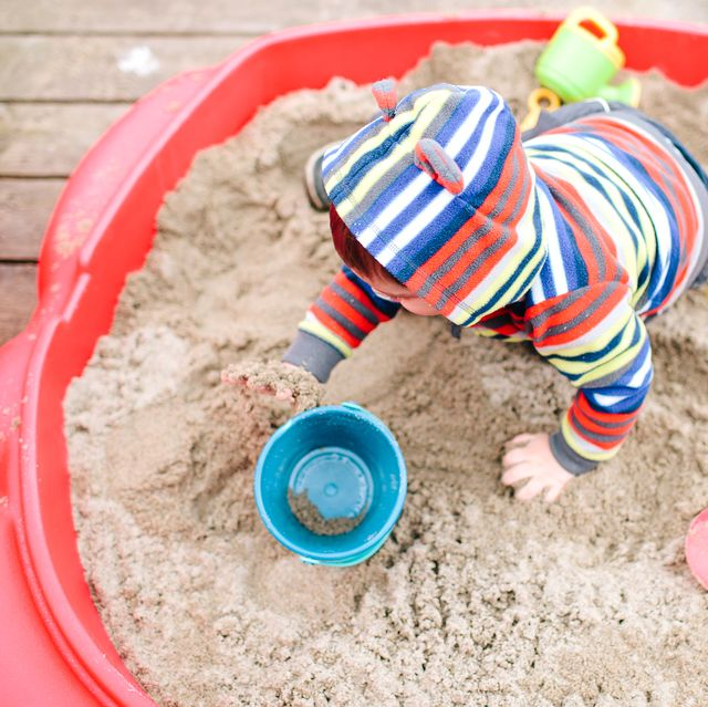 kid playing in sandbox with beach toys