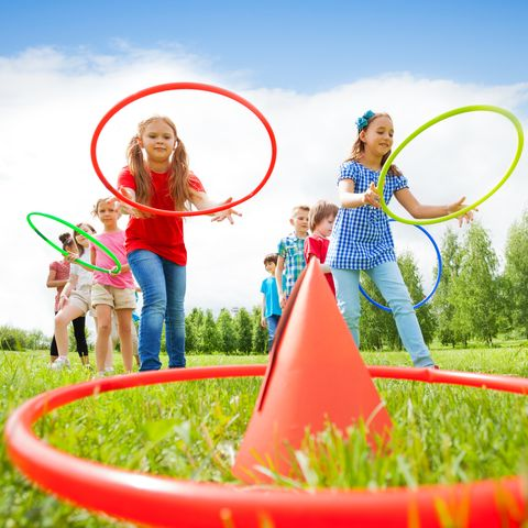 kids throw colorful hoops on cones while competing