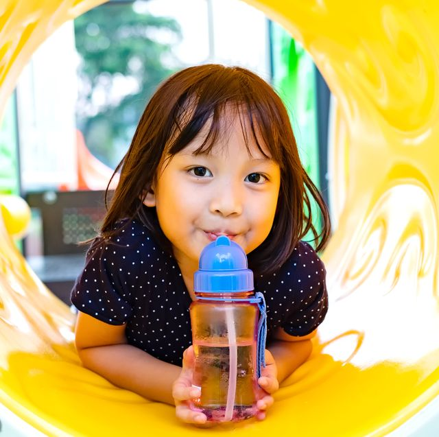 kid on playground sipping from water bottle