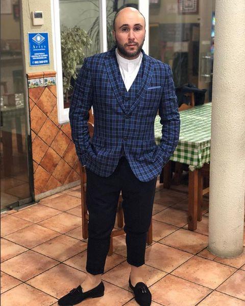 Clothing, Suit, Standing, Outerwear, Blazer, Formal wear, Jeans, Plaid, Jacket, Pattern,