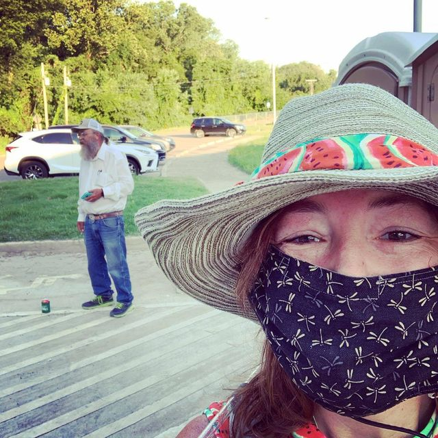 """kim mccoy wearing her straw, watermelon themed hat that she made for herself for the race pictured in the background is gary """"lazarus lake"""" cantrell"""