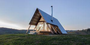 Una cabaña de madera en mitad de una colina