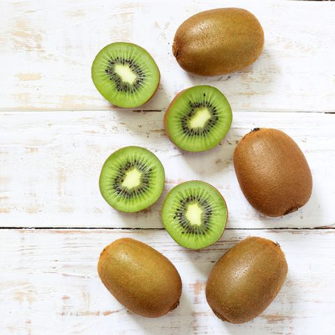 Kiwi fruit on white wooden background