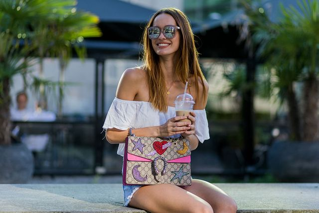 duesseldorf, germany   august 25  fashion model jueli mery drinking iced coffe on a summer evening jueli wearing white hm off shoulder top, gucci dionysus bag, zara denim shorts on august 25, 2016 in duesseldorf, germany photo by christian vieriggetty images