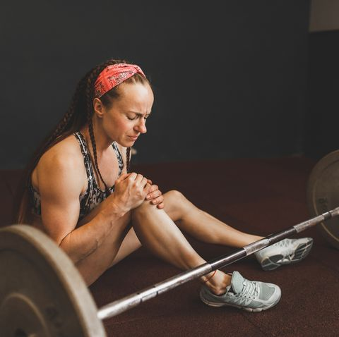 knee injury of woman lifting barbell in gym health problem, sprain ligament, stress and pain