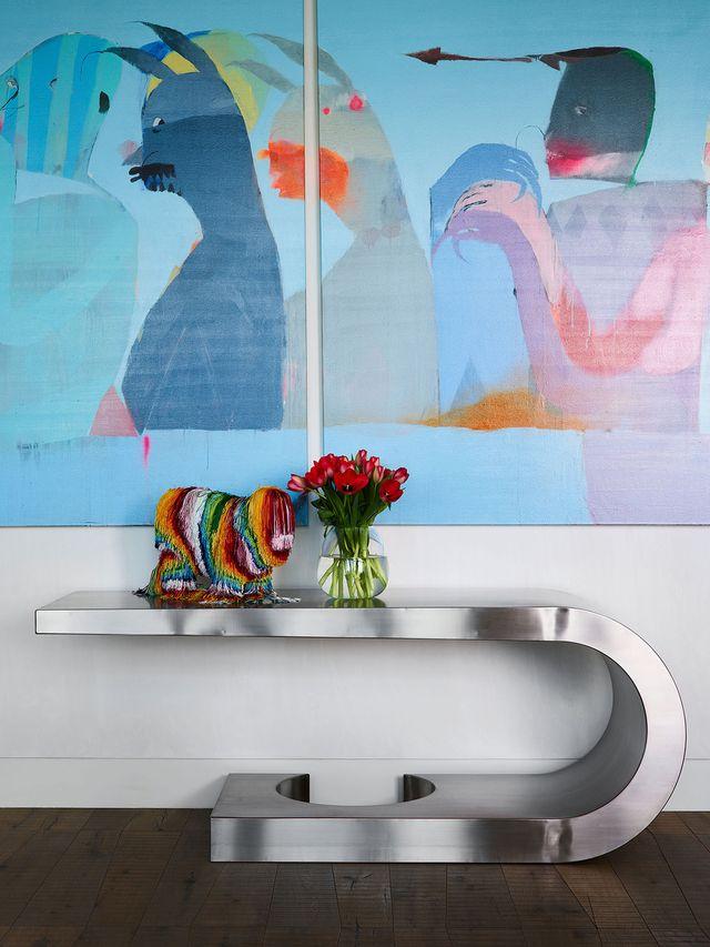 detalle de cuadro abstracto de colores vivos y consola plateada