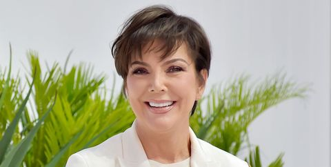 kris jenner smiling in front of palm fronds