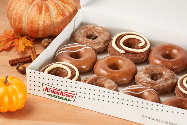 donuts in a box with pumpkins as decor near it