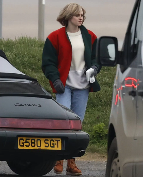 kristen stewart wears a black green and red bomber jacket over a crewneck sweatshirt blue jeans and tan lace up boots as princess diana on set for spencer film