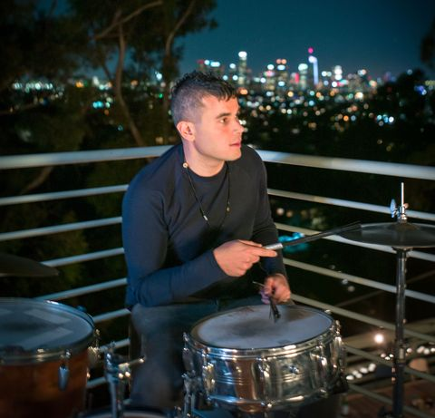 Rostam playing drums in front of the horizon
