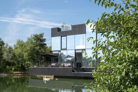 Una casa junto al lago de fachadas de cristal y sostenible