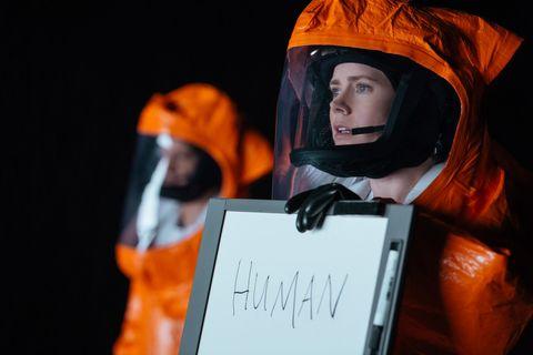 la protagonista de la llegada con una pizarra en la que indica que es humana