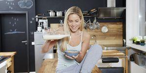 Vrouw schenkt melk in een bakje cereals