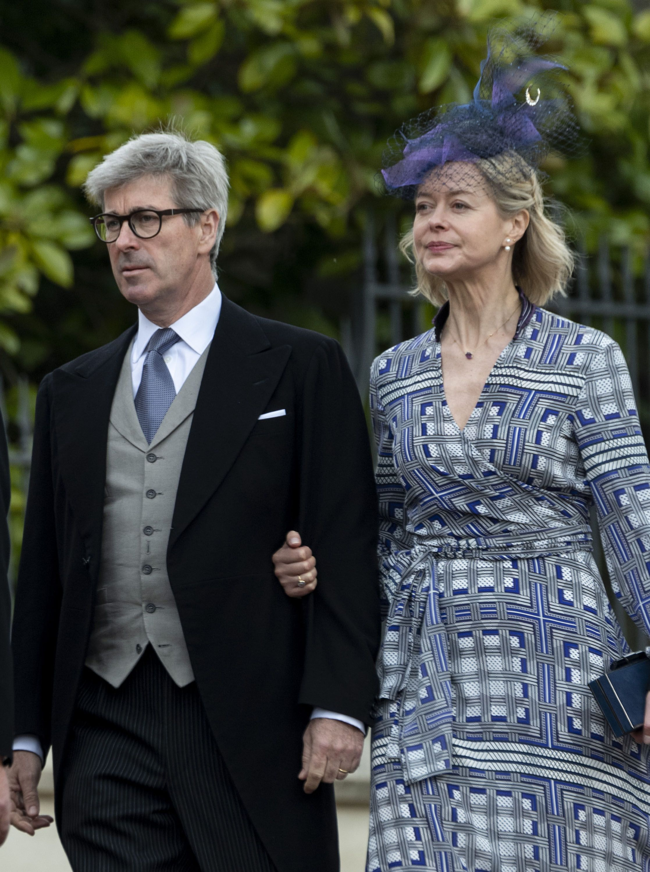 In a patterned wrap dress and blue netted fascinator.