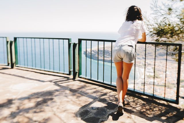 lady leaning against fence over the cliff