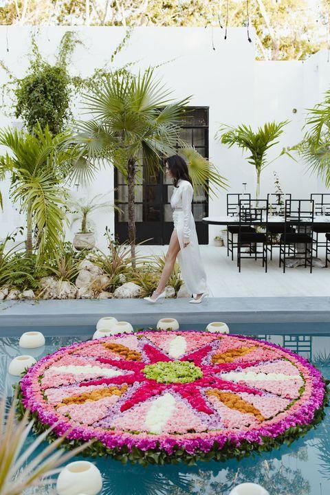 marchant au bord du mandala floral flottant de la piscine