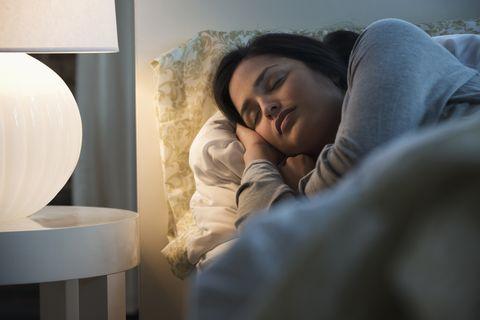 lamp illuminating sleeping hispanic woman