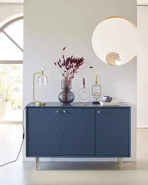 recibidor con cómoda azul y lámpara de mesa dorada