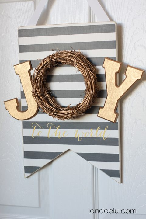 wooden joy to the world sign with gold j and y and the o made out of a grapevine wreath the letters are on a pennant shaped wood board painted with gray and white stripes and the words to the world