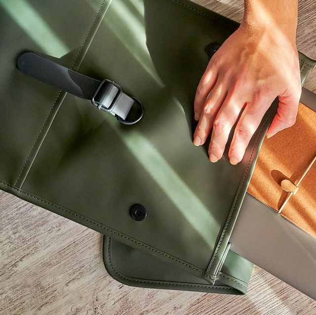 person pulling laptop and notebook out of green bag