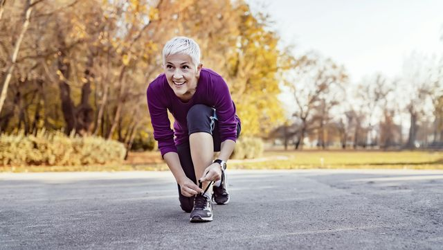 mujer atándose una zapatilla antes de salir a correr