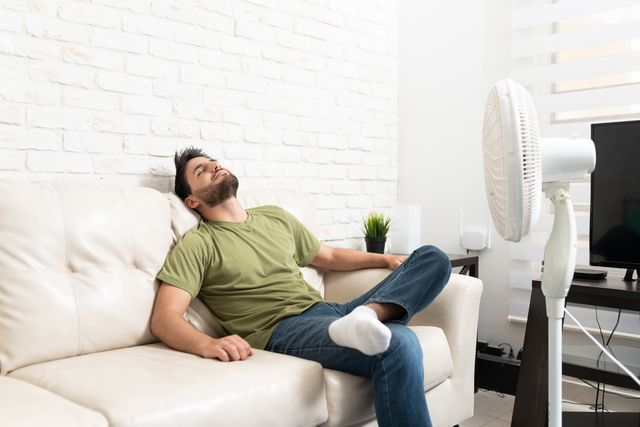 latin man relaxing in front of fan at home