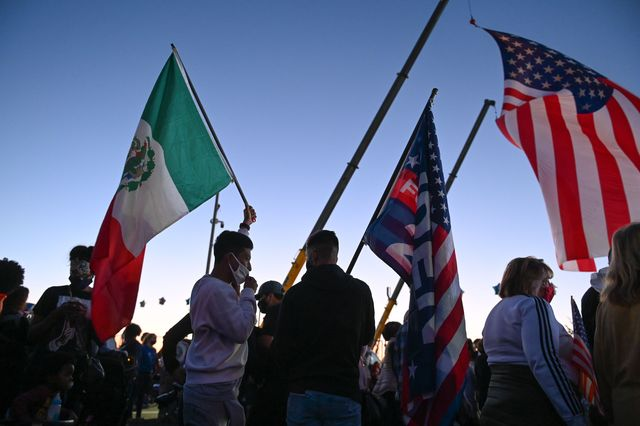 supporters of president elect joe biden hold us and mexican flags as they gather outside the chase center in wilmington, delaware on november 7, 2020 to celebrate   democrat joe biden has won the white house, us media said november 7, defeating donald trump and ending a presidency that convulsed american politics, shocked the world and left the united states more divided than at any time in decades photo by roberto schmidt  afp photo by roberto schmidtafp via getty images