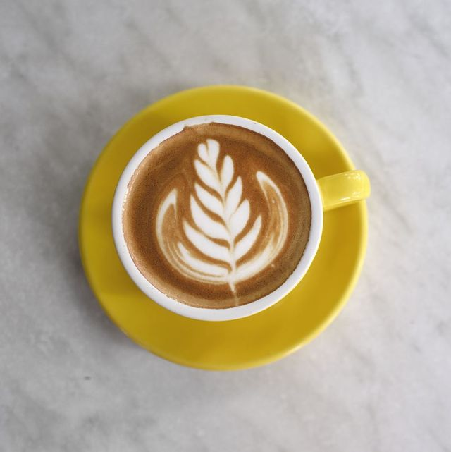 latte art in a yellow cup on a marble table