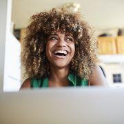laughing black woman using laptop