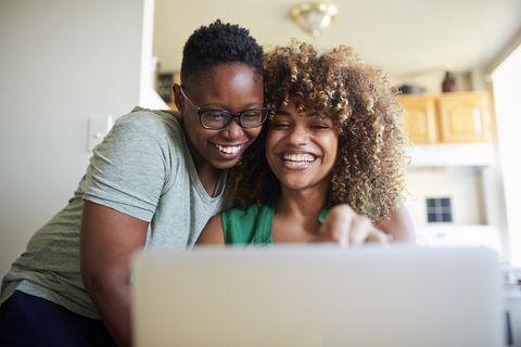 laughing black women hugging and using laptop