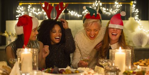 Laughing friends enjoying candlelight Christmas dinner