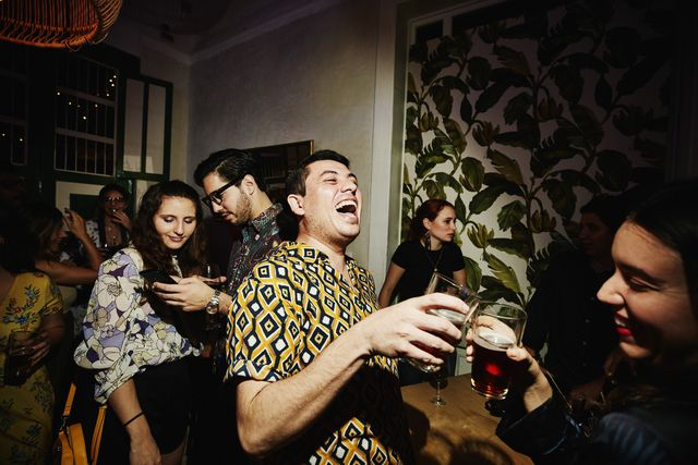laughing friends toasting during party in night club