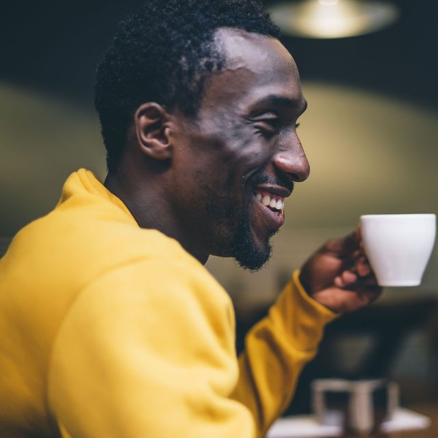laughing man with cup of coffee in a coffee shop