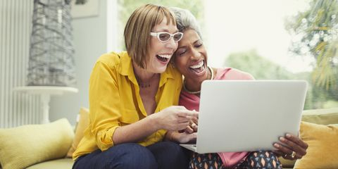 Laughing mature women sharing laptop on living room sofa