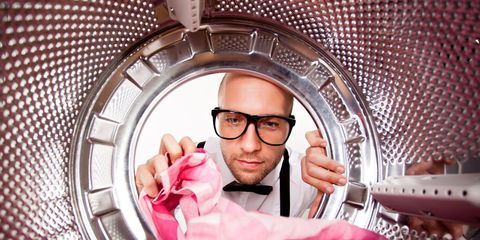 nerdy man peering into laundry machine
