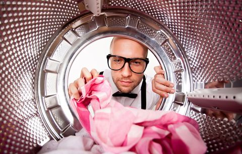 nerdy man peering into laundry machine