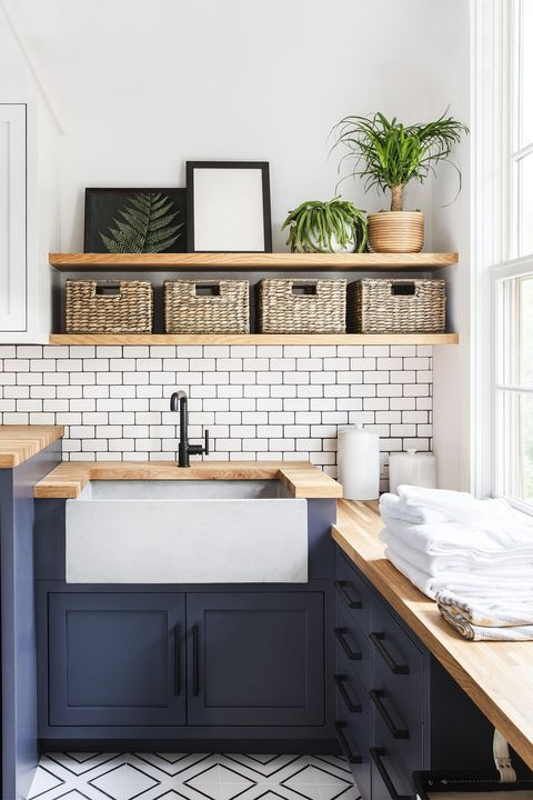laundry room with dark blue cabinets, subway tile, woven storage baskets, canisters, farmhouse sink designed by emilie munroe, studio munroe