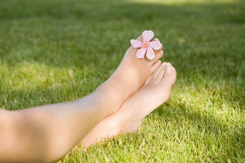 los pies de una mujer, en el césped, con una flor entre los dedos