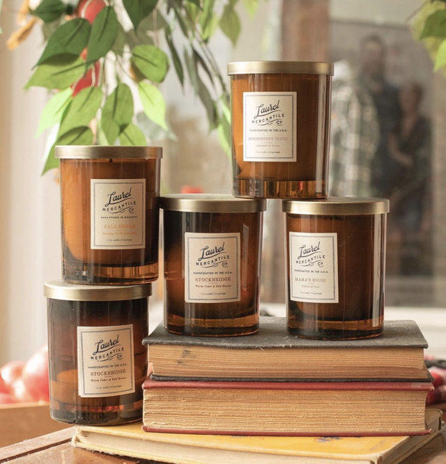 5 laurel mercantile fall candles displayed on books