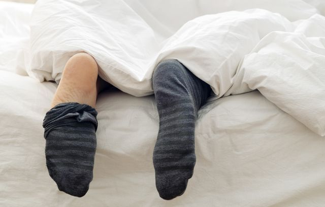lazy man removing his socks  on the bed