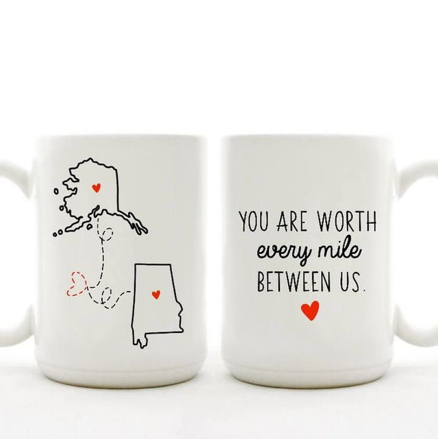 two big white coffee mugs, one has a picture of a map of alaska connected by a dotted line to a map of alabama the other reads you are worth every mile between us