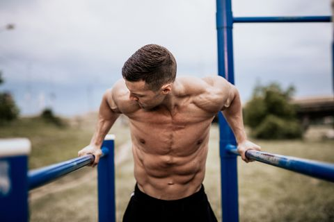 Young man doing dips in the local park