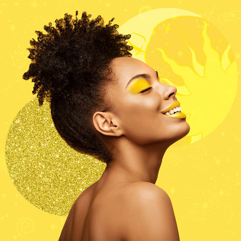 black woman smiling on yellow background with hair up