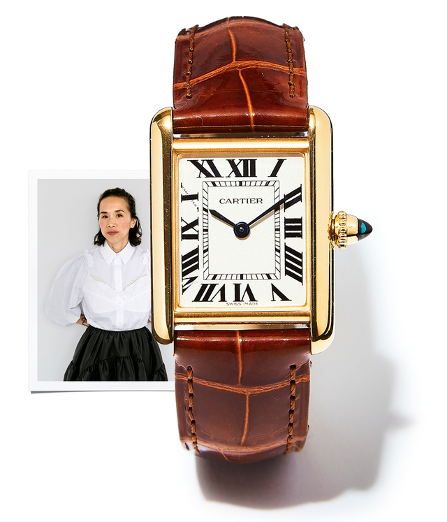 brown watch and picture of woman against white wall wearing white shirt and black skirt