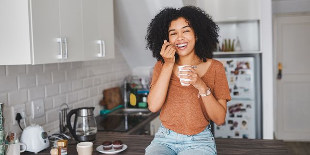 woman eating a yogurt in her kitchen
