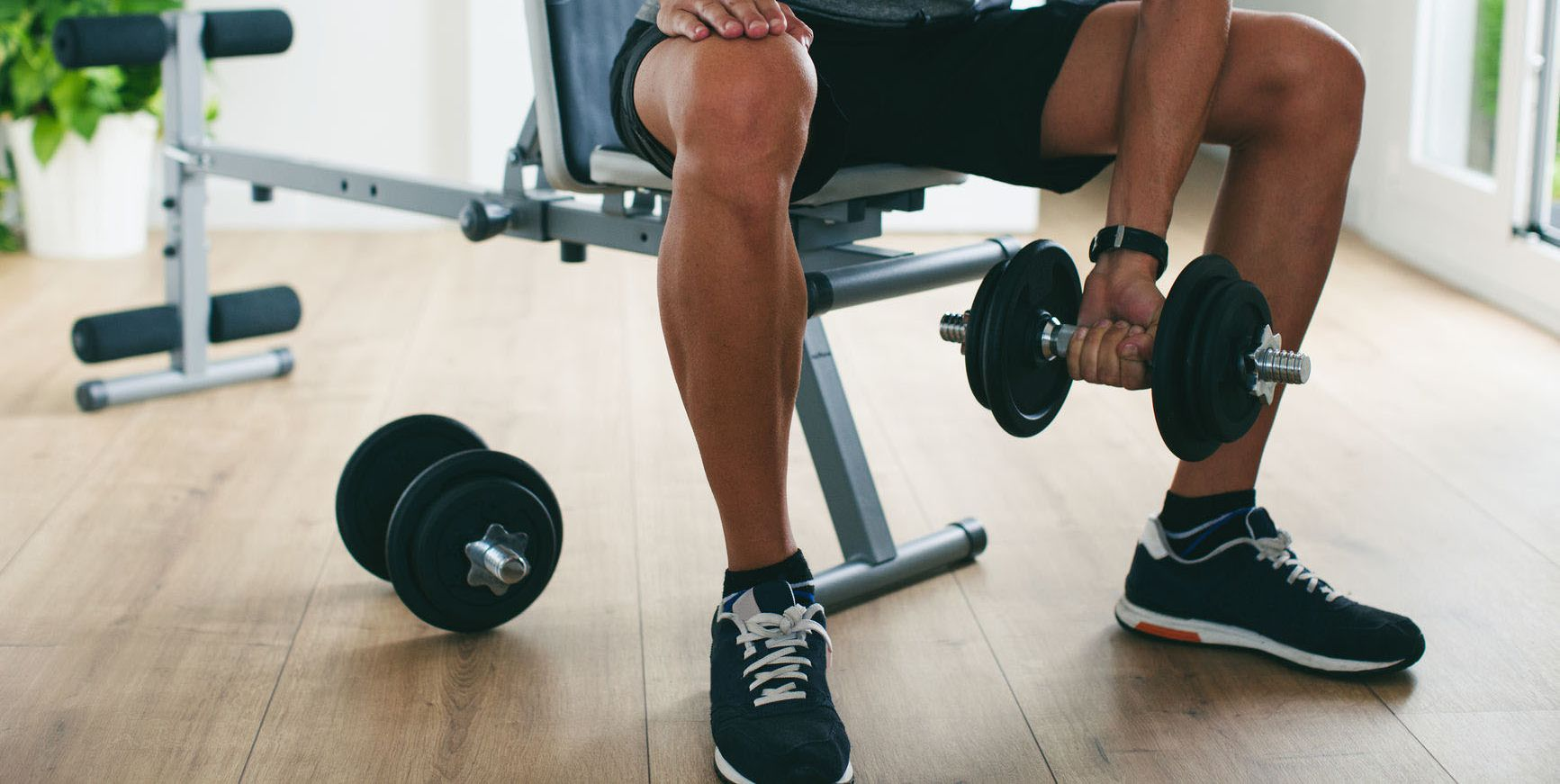 Closeup Of A Man Lifting Weights Sitting On A Workout Bench At Home.